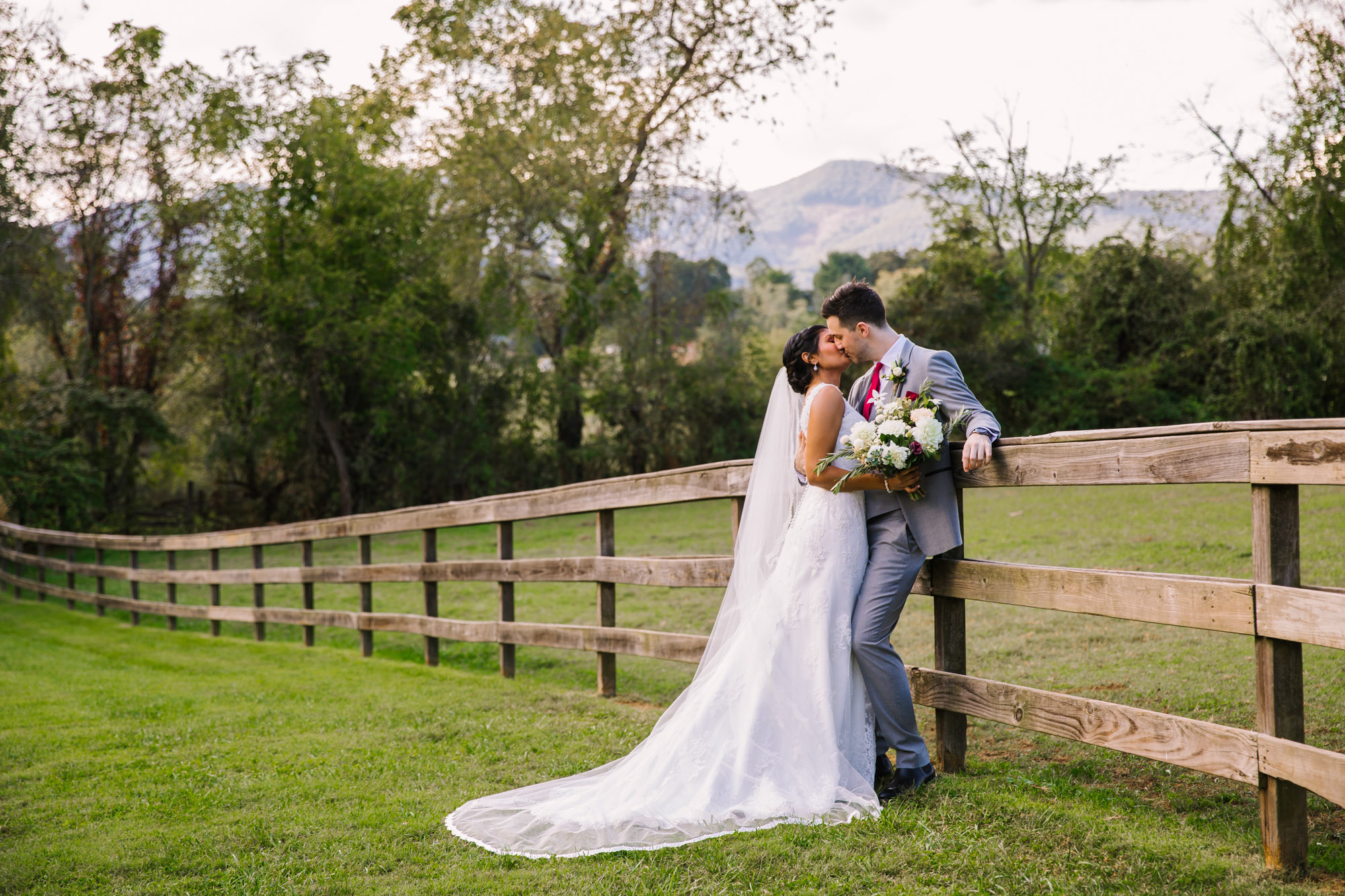 Waynesville NC Wedding Photography | Bride and Groom Kissing on the Fence line