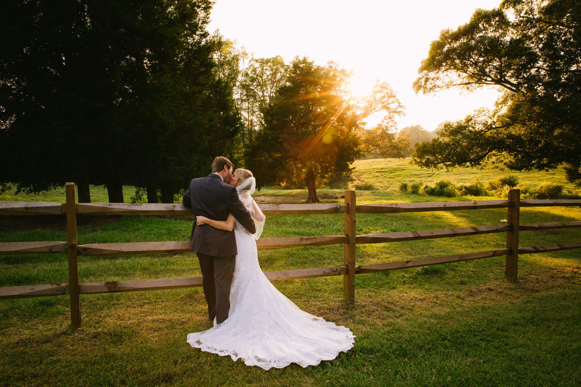 Waynesville, NC Wedding Photography | Bride and Groom kissing on the fence line