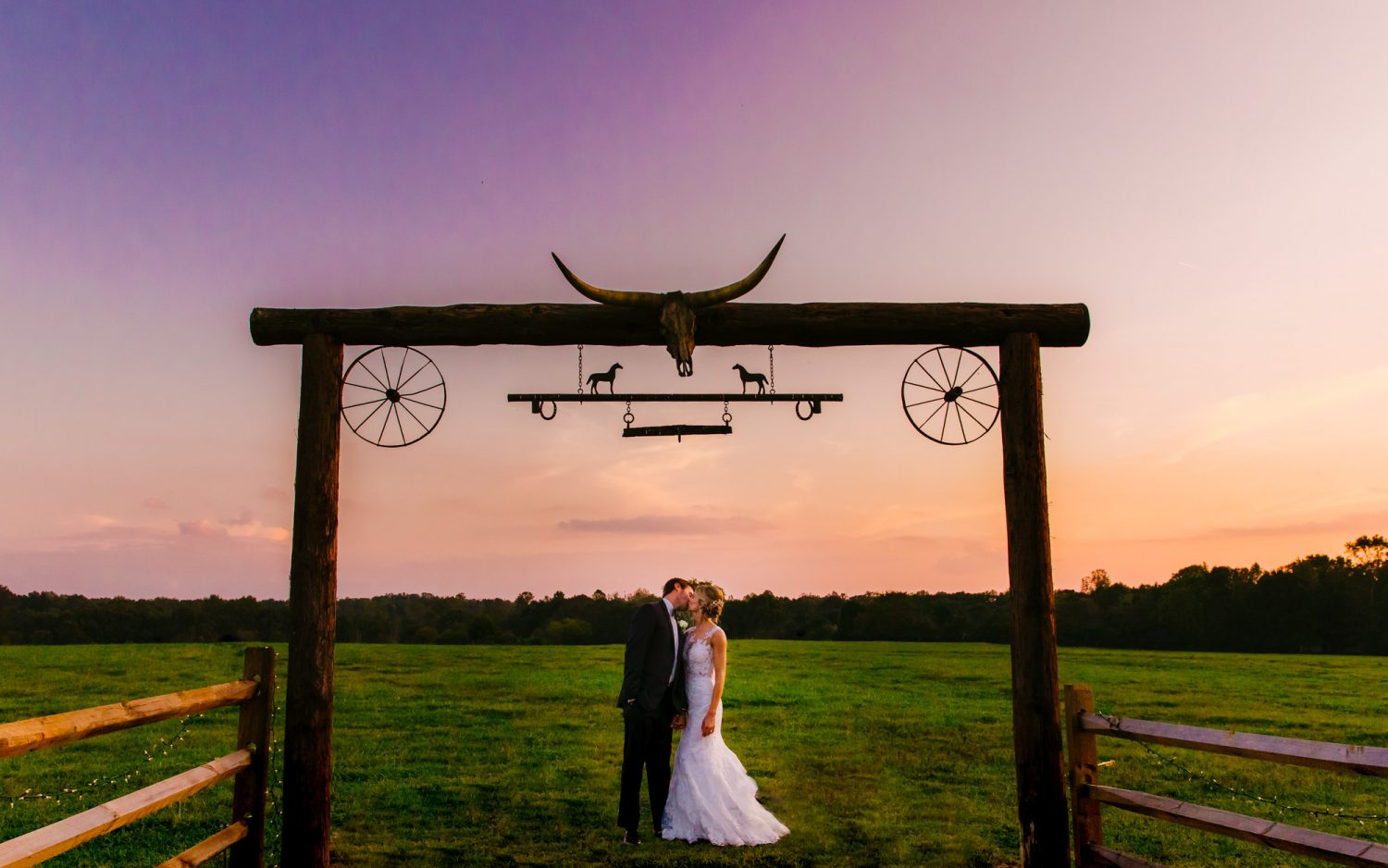 Waynesville, NC Wedding Photography | Bride and Groom Kissing at Pasture Entrance Multi-colored Sky
